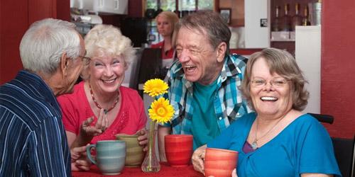 Seniors sitting together drinking from mug