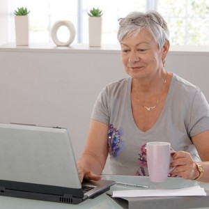 senior lady at the computer with the mug