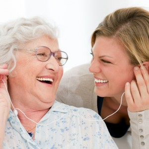 young lady and senior woman listening to music using earbuds